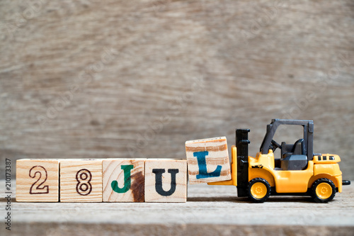 Poster  Toy forklift hold block l to complete word 28 jul on wood background (Concept fo