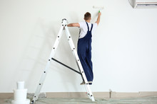 Male Painter Using Roller For ...