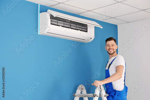 Electrician repairing air conditioner indoors Canvas Print
