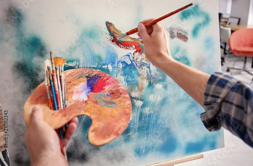 Fototapeta Male artist painting on canvas in workshop obraz