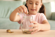 Little Girl Putting Coins Into...