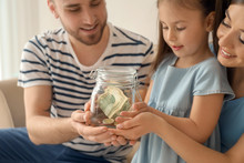 Little Girl With Her Parents Holding Glass Jar With Dollars Indoors. Money Savings Concept