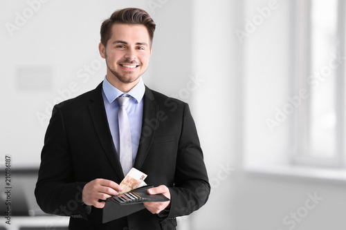 Fotografía  Young businessman counting money indoors. Money savings concept