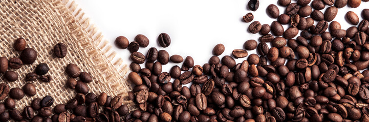 FototapetaPanoramic background of roasted coffee beans on a white background with a jute sack