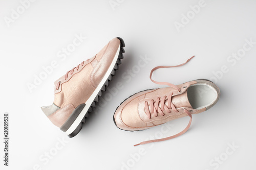 Fotografia  Pastel pink female sneakers on white background