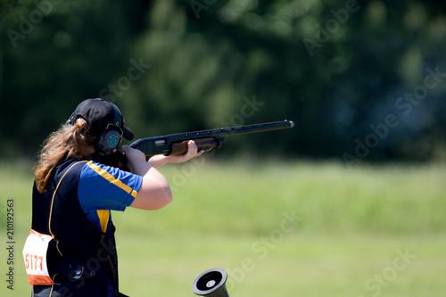 Fototapeta Teenage girl shooting in a shotgun competition.
