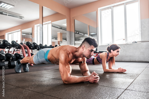 Fotografía  sporty couple doing plank exercise i the gym