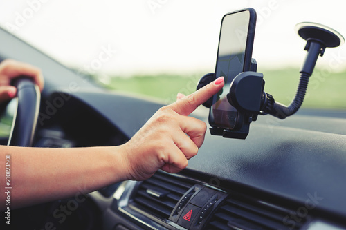 Fotografia  Kobieta używa nawigacji na swoim telefonie komórkowym w samochodzie