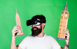 Leinwanddruck Bild - Man with beard in VR glasses, green background. 3D design concept. Guy holds Big Ben and Empire State Building. Man on smiling face creates architecture, rendering 3D design in virtual reality