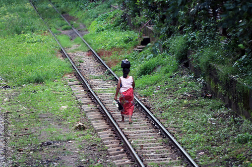 Fototapeta Behind of Myanmarese lady villager walking on the railroad tracks and put the black bag or belongings on the head