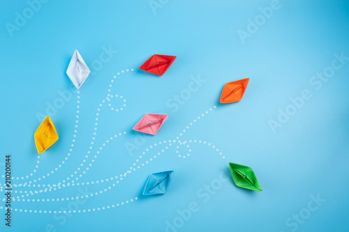 Obraz Paper ships on blue background. Business competition, different vision creative and Innovative solution for business concepts. - fototapety do salonu