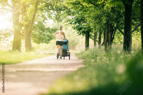 Fotografia, Obraz  Running woman with baby stroller enjoying summer in park