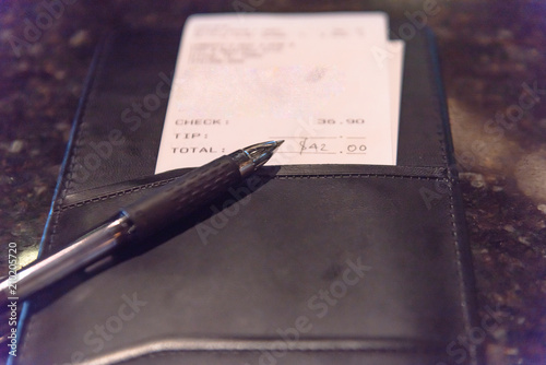 Fotografie, Obraz  Open leather check holder with restaurant bill and pen