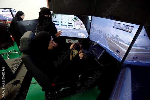 A driving instructor teaches a trainee on a simulator car