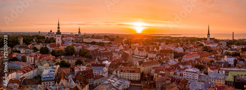 Foto auf Leinwand Violett rot Beautiful orange sunset over old town of Tallinn in Estonia with the Raekoja plats, castle and old medieval towers.