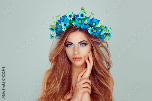 Beauty girl hand on face blue flowers on head in set combination with her nails