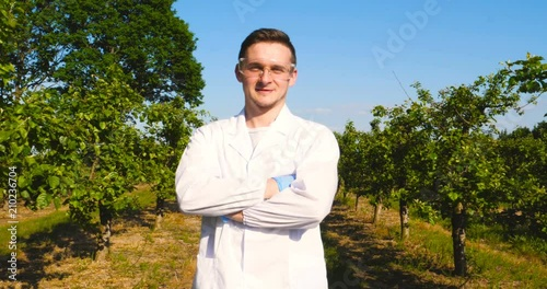 Valokuva  A young handsome (male) biologist or agronomist, wearing a white coat, wearing goggles, wearing blue rubber gloves, walks across the apple tree, the background of nature and greenery