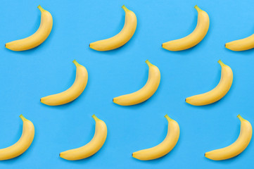 Minimalist pattern, fresh fruit and colorful art concept with flat lay top view of multiple yellow bananas isolated on bright blue background