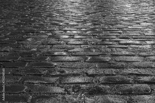 Cuadros en Lienzo Old wet illuminated cobblestone road on a rainy night