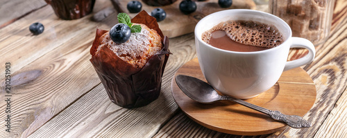 Poster Chocolate Muffins with blueberries and a cup of hot chocolate on a wooden background. homemade baking. Banner