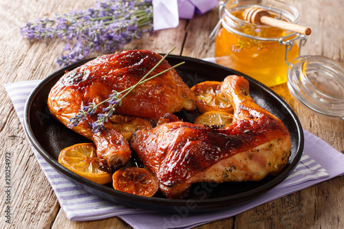 French food: fried quarters chicken legs with lavender honey, spices and lemon close-up Wallpaper Mural