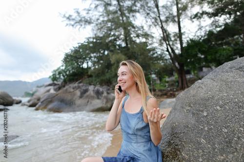 Fotobehang UFO Young caucasian girl sitting on sand near sea and stones, speaking by smartphone. Concept of modern technology and resting on beach in morning.