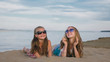 Two teenage are sitting on a sandy beach near the sea. Girl playing, talk to each other. Sisters are dressed in dresses and sunglasses. Children have real emotions of happiness.
