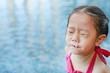 canvas print picture - Mucus flowing from nose of little asian child girl while swimming at pool.