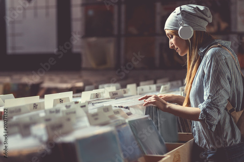 Poster de jardin Magasin de musique Attractive girl listening to music in a music store