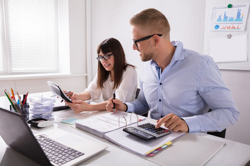 Fototapeta Two Businesspeople Calculating Invoice