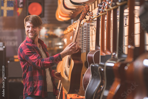 Photo Stands Music store Smiling young man with a guitar indoors