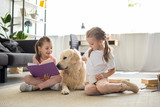 Fototapeta Zwierzęta - little sisters with books and golden retriever dog near by sitting on floor at home