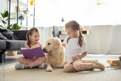 little sisters with books and golden retriever dog near by sitting on floor at h Canvas Print