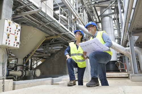 Valokuva  Industrial workers in factory checking blueprint