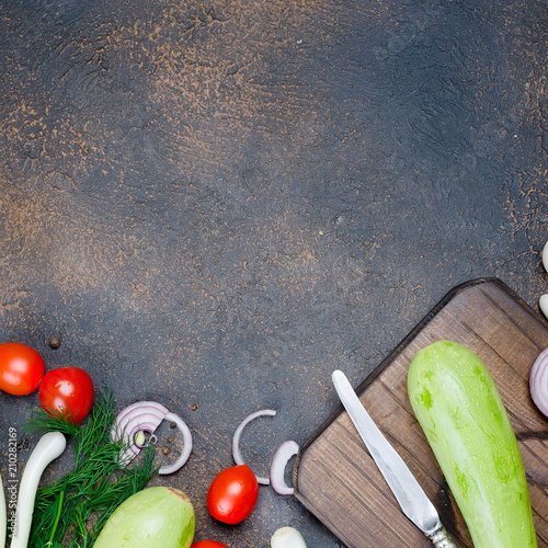 Young spring zucchini, tomatoes, herb and spices on black background