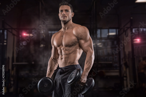 Fotografie, Obraz  Young handsome sportsman bodybuilder weightlifter with an ideal body, after coaching poses in front of the camera, abdominal muscles, biceps triceps