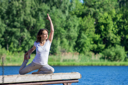 Young Caucasian Woman Doing Yoga Asanas Outdoors On A Wooden Pier By The River Or Lake Sunny Summer Morning Wearing No Makleup And Sports Clothes Buy This Stock Photo And Explore
