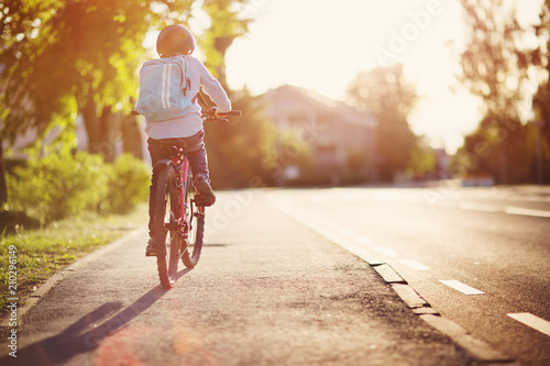 child on a bicycle at asphalt road in early morning. Boy on bike in the city