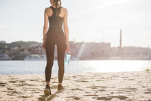 Back View Of Athletic Woman With Sports Bottle Of Water Walking On Beach With Backlit