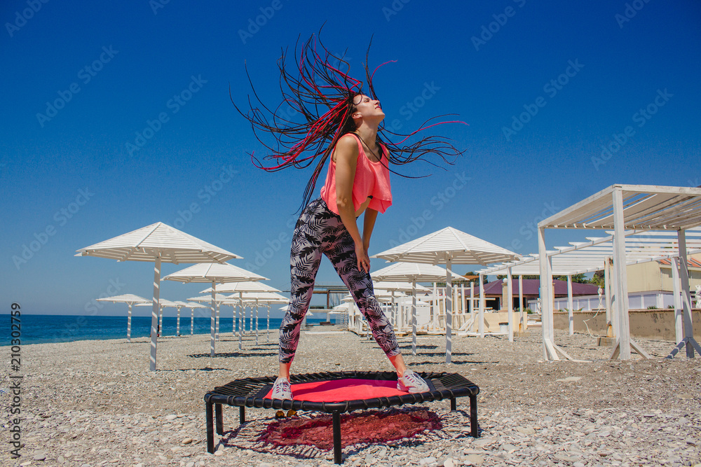 Photo Art Print A Slim Athletic With Dreadlocks Jumping On Fitness Trampoline Outdoors Pebble Beach By The Sea Abposters