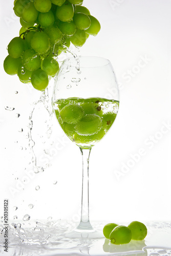 Green grape with water splash into glass
