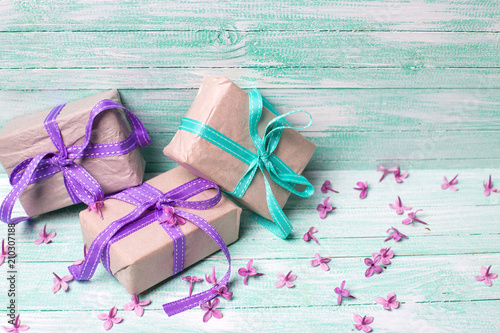 Festive gift boxes and lilac flowers on turquoise wooden background.