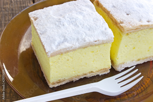 Fotografie, Obraz  Cream pie with layers of puff pastry in plate on wooden table