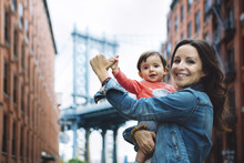 USA, New York, New York City, Happy Mother Holding A Baby In Brooklyn With Manhattan Bridge In The Background