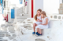 Two Sisters Sitting On The Stairs On The Greek Street