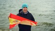 Slow motion portrait of happy Spanish sports fan holding national flag of Spain standing on sea coast and smiling. Patriotism, active lifestyle and people concept.