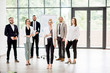 Portrait of a group of business people standing during a conference with flip chart at the modern office
