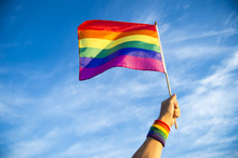 Colorful Rainbow Gay Pride Flag Being Waved In The Breeze  By A Hand Wearing A Sweatband