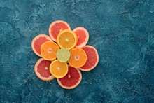 Top View Of Stacked Various Citrus Fruits Slices On Blue Concrete Surface