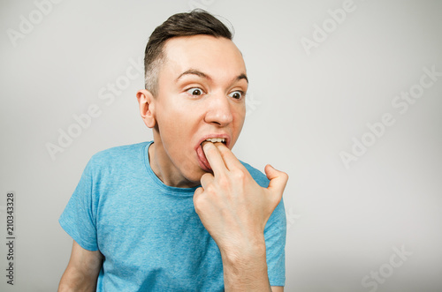 Valokuva  Young guy inserts two fingers in the mouth to induce vomiting, on a light background